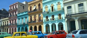 Havana - July 31: colorful cars parked in front of historic buildings in Havana, Cuba on July 31, 2014. The architecture and classic cars of Havana are a major tourist attraction.